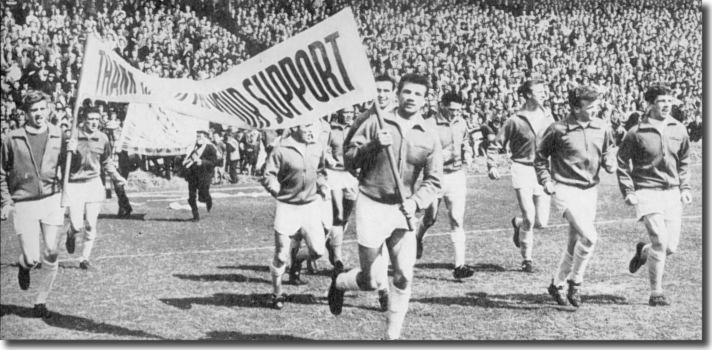 The Leeds players take to the field for a lap of honour before the final home game with Plymouth - Gary Sprake and Paul Reaney carry the banner of thanks - also in shot are Hunter, Collins, Johanneson, Bell, Weston, Charlton, Bremner, Giles
