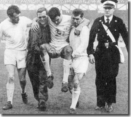 Willie Bell is chaired off by Les Cocker and Johnny Giles with Jim Storrie and the Red Cross in close attendance during the bruising encounter at Everton