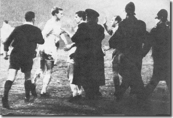 Team mate Rod Belfitt and the police try to hold Charlton off during a controversial incident against Valencia in 1966