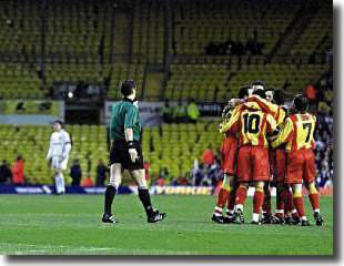 In front of the deserted section of Elland Road reserved for supporters who were subsequently banned, the Galatasaray players celebrate Hagi's early penalty