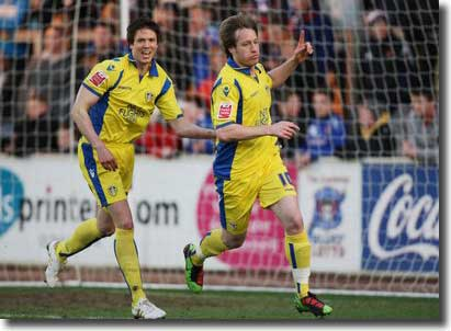 Leigh Bromby shows his delight as Luciano Becchio wheels away after opening the scoring at Brunton Park