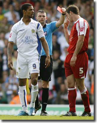 Jermaine Beckford looks on as referee Michael Oliver shows a red card to David McCracken of MK Dons