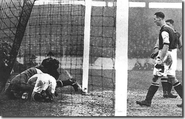 Tom Jennings charges West Ham goalkeeper Ted Hutton over his own line during an FA Cup tie at Upton Park in January 1930