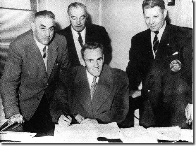 Bill Lambton (far right) watches as Don Revie signs for Leeds United