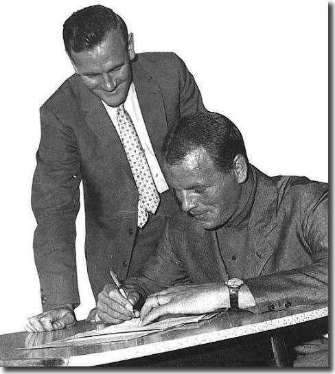Watched by his new manager Don Revie, Charles signs to confirm his return to Elland Road