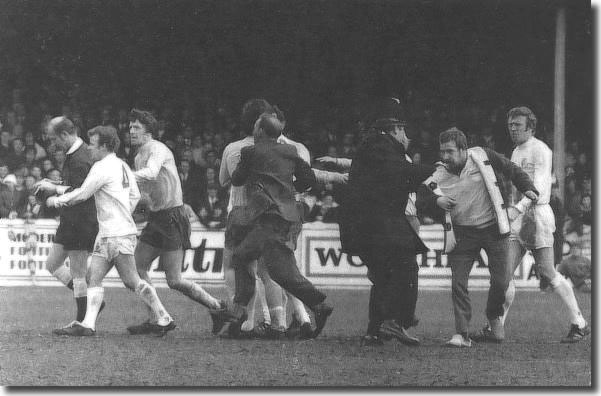 "Billy Bremner remonstrates with referee Ray Tinkler while police and fans tussle following the ""offside"" goal by West Bromwich Albion"