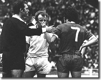 The referee calls Bremner and Keegan together before dismissing them