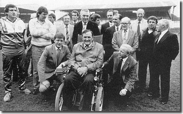Revie, now crippled with Motor-Neurone disease, surrounded by ex-players following a reunion in 1988.  He is flanked by Allan Clarke and Billy Bremner with Norman Hunter and David Harvey on the left, Joe Jordan at the back, Mick Bates, Paul Madeley and Terry Cooper half hidden and Jack Charlton, Johnny Giles and Bobby Collins on the far right