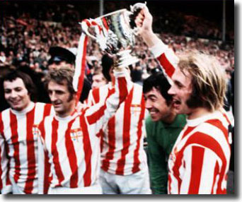 Jimmy Greenhoff and George Eastham hoist the League Cup - also pictured are full-back John Marsh and Gordon Banks