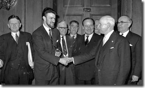 The PFA's Jimmy Hill shakes hands with League President Joe Richards during the negotiations on the maximum wage - Hardaker is on the left
