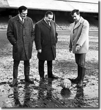 Different day, same old mud at Ninian Park, as Welsh referee Clive Thomas tries to decide whether it is playable