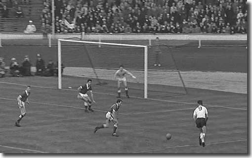 Alan Peacock moves onto the ball before unleashing an unstoppable shot from the right to beat Wales keeper Millington during a 4-0 victory in November 1962